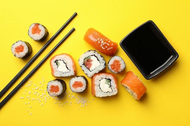 Rolos de sushi, pauzinhos e soja na mesa amarela, vista superior