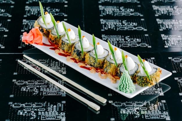 Rolos de sushi quente cobertos com maionese japonesa tobiko vermelho e cebolinha