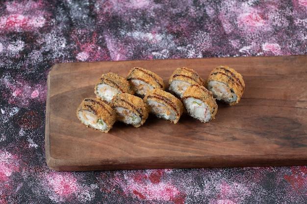 Rolos de sushi quente com cream cheese em uma placa de madeira.