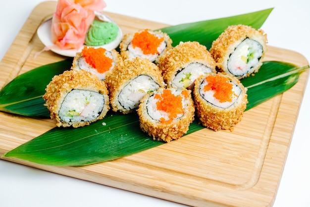 Rolos de sushi quente com palitos de caranguejo, abacate servido nas folhas na placa de madeira