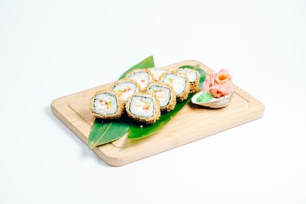Rolos de sushi quente com tempura e abacate servido nas folhas na placa de madeira