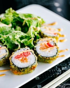 Rolos de sushi quentes com salmão e gengibre, guarnecidos com maionese picante