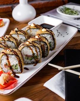 Rolos de sushi quentes servidos com molho de soja, gengibre e wasabi 1