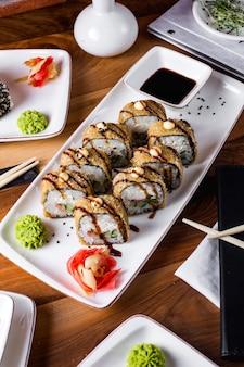 Rolos de sushi quentes servidos com molho de soja, gengibre e wasabi