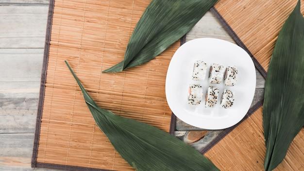 Rolos de sushi saboroso tradicional em chapa branca com placemat e folhas na mesa de madeira