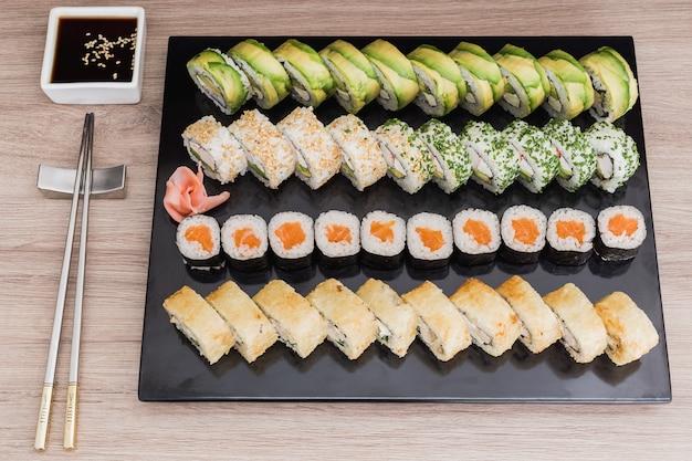 Rolos de sushi, saquê, califórnia, tempura com molho de soja em uma mesa de madeira
