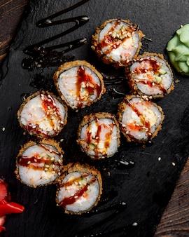 Rolos de sushi servidos com molho de wasabi e gergelim