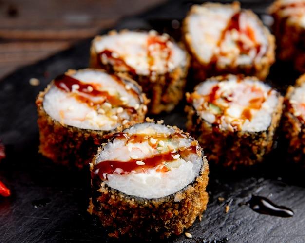 Rolos de sushi servidos com molho e gergelim