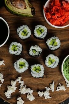 Rolos de sushi servidos na placa de madeira com vista superior de ingredientes clássicos