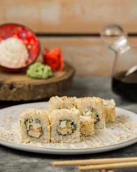 Rolos de sushi tempura cobertos com gergelim e molho