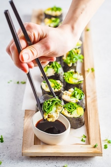 Rolos de sushi verde vegano com abacate