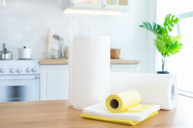 Rolos de toalhas de papel, limpando toalhetes e sacos de lixo em cima da mesa na cozinha com a luz solar.