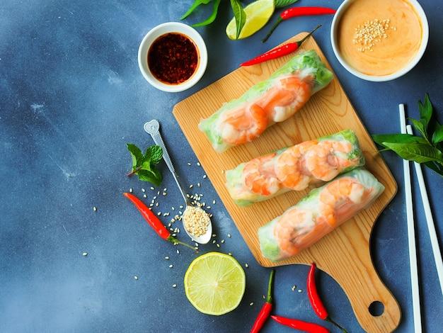 Rolos de verão frescos com camarão e vetgetables, comida vietnamita em vista superior com espaço de cópia.