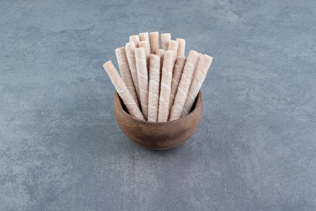 Rolos de wafer saborosos em uma tigela de madeira.