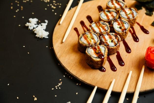 Rolos fritos de vista lateral com molho em um carrinho com wasabi