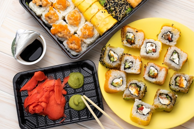 Rolos na placa amarela com wasabi e molho de soja na mesa da placa de madeira. um marisco com pauzinhos.