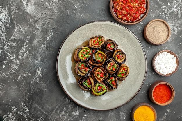 Rolos recheados de berinjela recheada com especiarias em pequenas tigelas sal pimenta pimenta vermelha cúrcuma adjika na superfície cinza