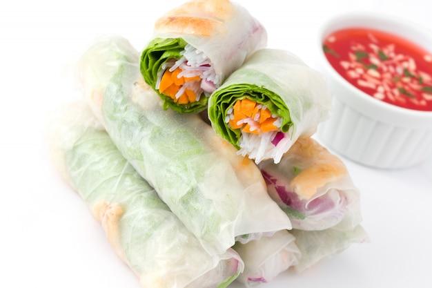 Rolos vietnamitas com legumes, macarrão de arroz e camarão com molho de pimentão doce na superfície branca