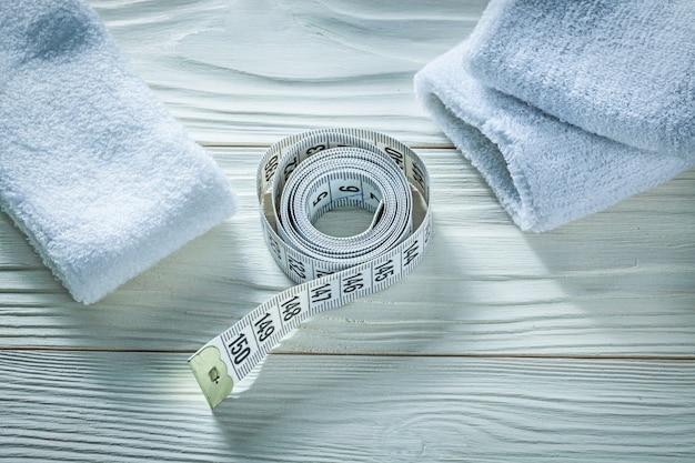 Rolou a fita de medição sweatbands na placa de madeira conceito de treinamento esportivo