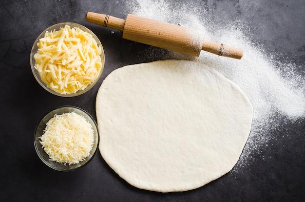 Rolou a massa, assar farinha, queijo ralado e rolling pin em um quadro negro escuro.