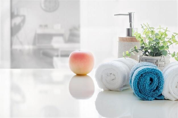Rolou de toalhas limpas na tabela branca com borrão da sala de visitas, espaço da cópia para a exposição do produto.