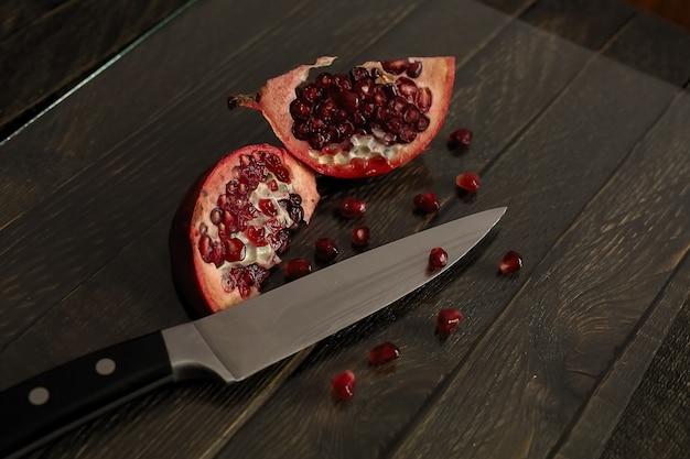 Romã aberta sobre uma mesa de madeira. romã fatiada e faca de cozinha.