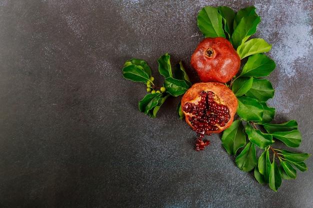 Romã com sementes e folhas em fundo escuro.