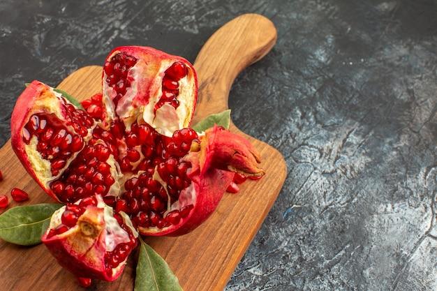 Romã cortada em fatias de frutas vermelhas frescas em piso claro de frutas vermelhas frescas