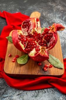 Romã cortada em fatias de frutas vermelhas frescas na mesa claro-escuro frutas vermelhas frescas