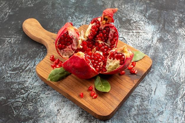 Romã cortada em fatias de frutas vermelhas frescas na mesa de luz frutas vermelhas frescas