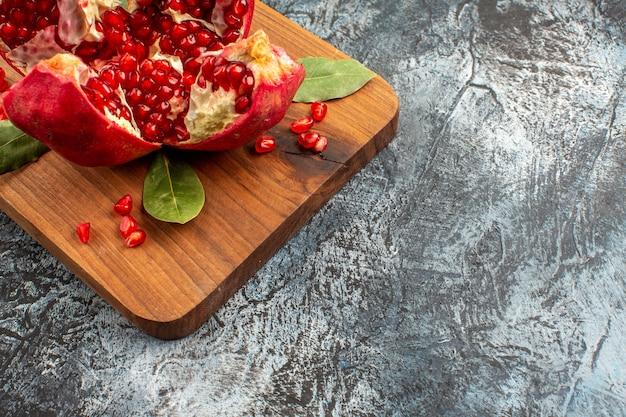 Romã cortada em fatias de frutas vermelhas frescas na mesa de luz