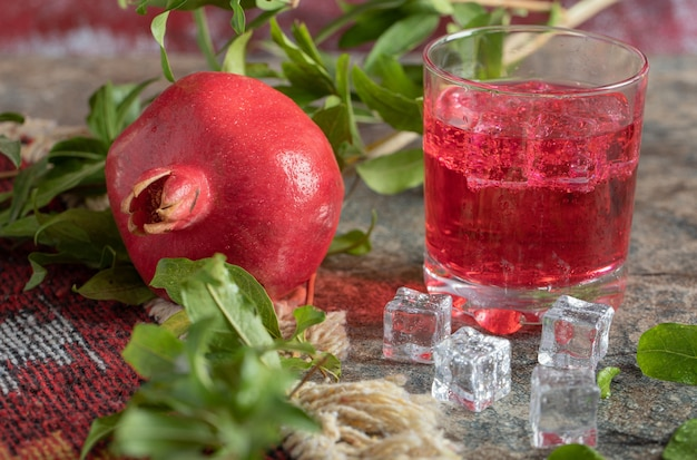 Romã e copo de suco na mesa de pedra com folhas