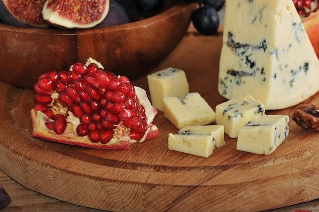 Romã e queijo azul em uma superfície de madeira