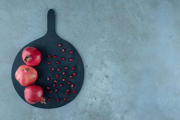 Romã e sementes vermelhas em uma bandeja preta.