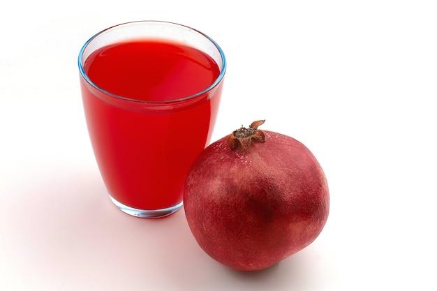 Romã e suco em um copo sobre uma superfície branca