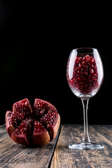 Romã em copo de vinho na mesa de madeira