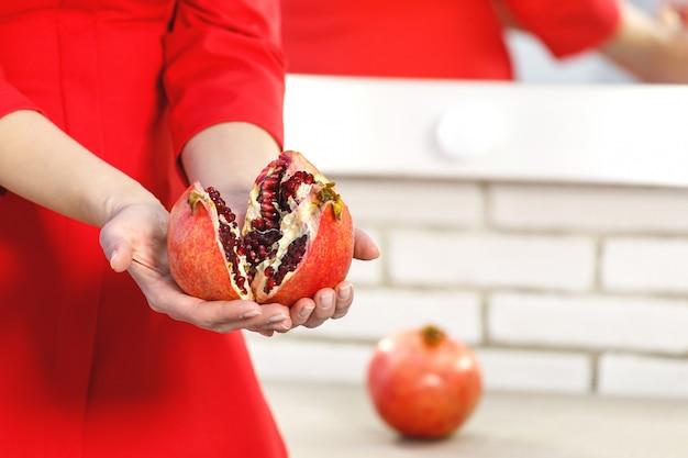 Romã em mãos femininas. uma mulher vestida de vermelho segurando dois nadadores de romã, uma fruta inteira no pedestal branco