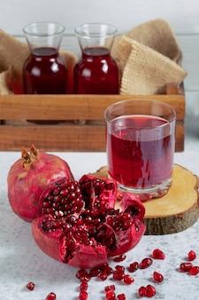 Romã fatiada e inteira orgânica com copos de suco fresco.