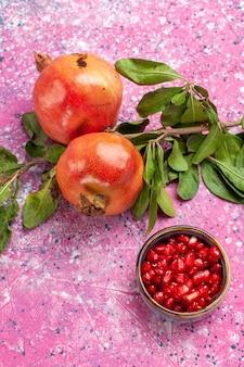 Romã fresca com folhas verdes na superfície rosa