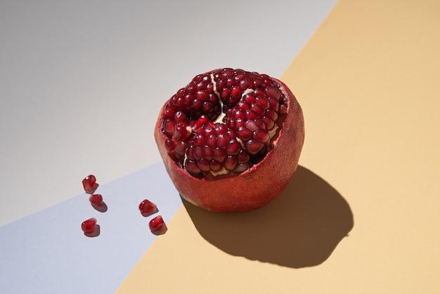 Romã fresca doce em um fundo colorido com uma sombra dura