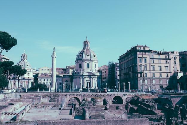 Roma, itália - 20 de junho de 2018: vista panorâmica do fórum e coluna de trajano em roma, longe da igreja do santíssimo nome de maria. dia de verão e céu azul