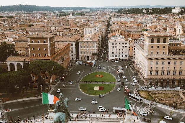 Roma, itália - 21 de junho de 2018: vista panorâmica da piazza venezia e da cidade do monumento vittorio emanuele ii, também conhecido como vittoriano, em roma. carros de trânsito e dia de verão com céu azul