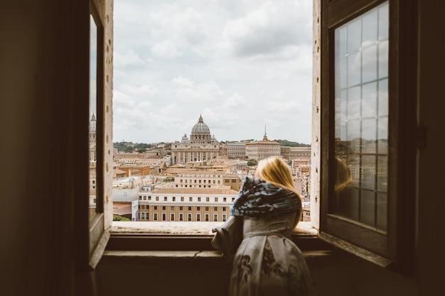 Roma, itália - 22 de junho de 2018: mulher observa da janela da basílica papal de são pedro (basílica de são pedro) no vaticano e na cidade de roma