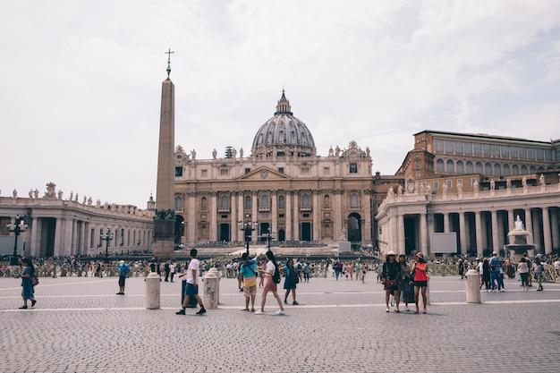 Roma, itália - 22 de junho de 2018: vista panorâmica sobre a basílica papal de são pedro (basílica de são pedro) no vaticano e a praça de são pedro. dia de verão e pessoas passeando