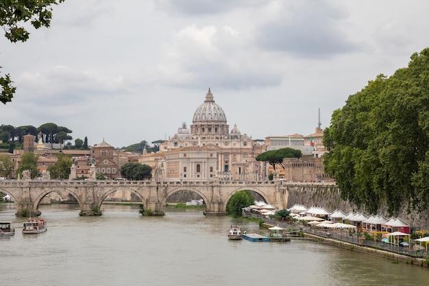Roma, itália - 22 de junho de 2018: vista panorâmica sobre a basílica papal de são pedro (basílica de são pedro) no vaticano e o rio tibre com ponte em roma. dia de verão