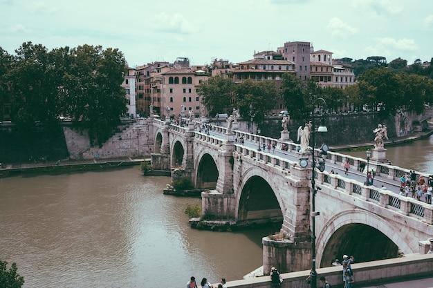 Roma, itália - 22 de junho de 2018: vista panorâmica sobre a ponte do castel sant'angelo e o rio tibre, em roma. dia de verão