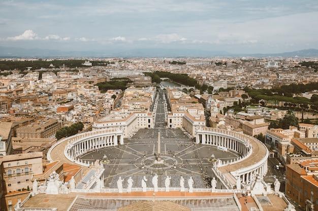 Roma, itália - 22 de junho de 2018: vista panorâmica sobre a praça de são pedro e a cidade de roma da basílica papal de são pedro (basílica de são pedro). dia de verão e as pessoas andam na praça