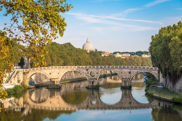 Roma, itália - circa de agosto de 2020: ponte sobre o rio tibre com a cúpula da basílica do vaticano no fundo e a luz do nascer do sol.