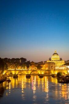 Roma, itália - junho de 2020: panorama do pôr do sol na ponte do rio tibre com a cúpula da catedral de são pedro (cidade do vaticano) no fundo - roma, itália