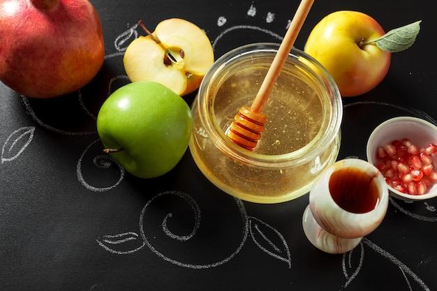 Romã, maçã e mel para símbolos tradicionais do feriado rosh hashaná (feriado de ano novo judaico) em fundo preto